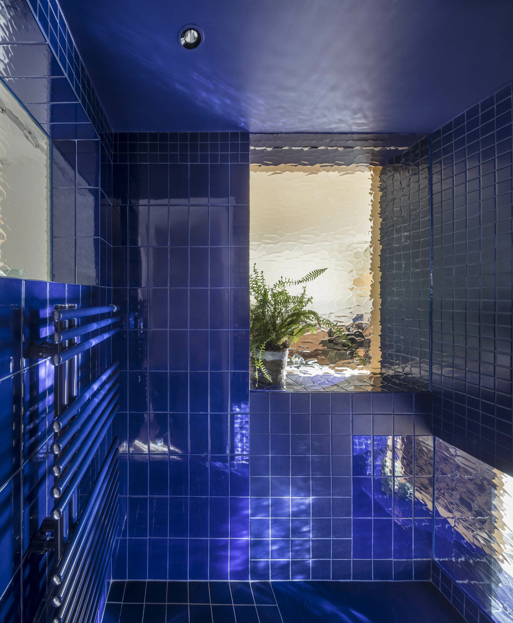 Daylight enters blue-tiled bathroom